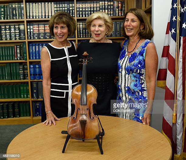 Nina Jill and Amy Totenberg pose with the stolen Stradivarius violin belonging to the late renowned violinist Roman Totenberg displayed at a news...