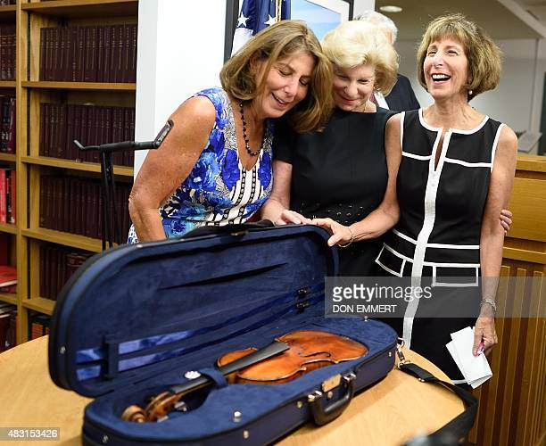Nina Jill and Amy Totenberg smile as they view the stolen Stradivarius violin belonging to their late father renowned violinist Roman Totenberg at a...