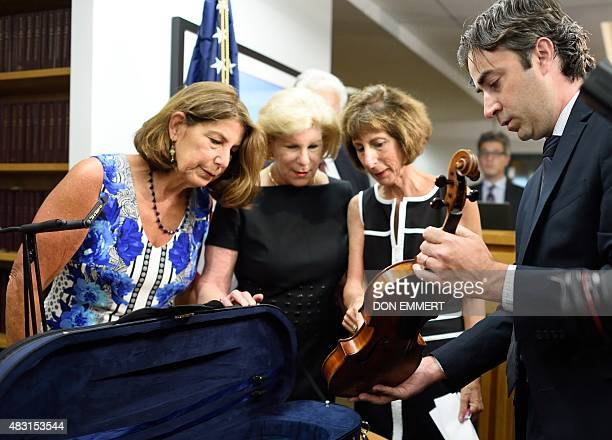 Nina Jill and Amy Totenberg view the stolen Stradivarius violin held by FBI agent Chris McKeogh belonging to their late father renowned violinist...