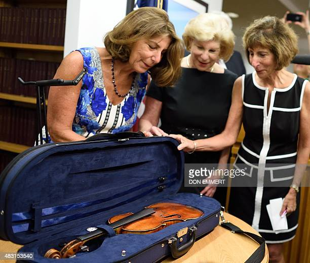 Nina Jill and Amy Totenberg view the stolen Stradivarius violin belonging to their late father renowned violinist Roman Totenberg at a news...