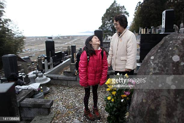Nina Kanno jokes around with her grandmother Mieko Kanno after laying flowers for relatives that were killed in the tsunami at Jodoji temple on March...