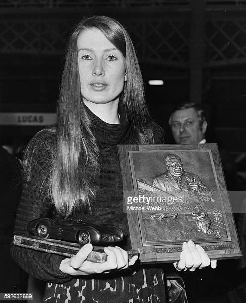 Nina Rindt the widow of racing driver Jochen Rindt holding a plaque and trophy honoring her husband's victory in the 1970 World Championships...