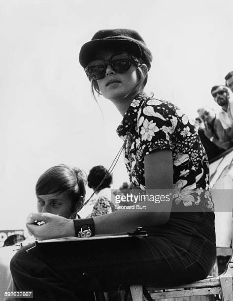 Nina Rindt wife of racing driver Jochen Rindt wearing a hat and large sunglasses as she watches her husband on the track during practice for the...