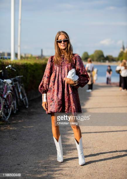 Nina Sandbech is seen wearing dress with print white bag cowboy boots outside MUF10 during Copenhagen Fashion Week Spring/Summer 2020 on August 06...