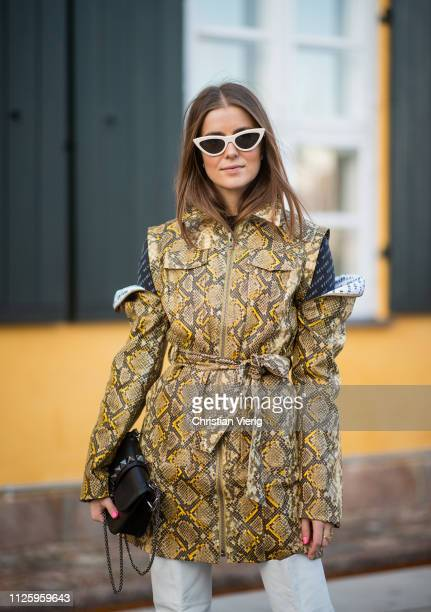 Nina Sandbech is seen wearing jacket with snake print and slits on the shoulders white overknees boots black Valentino bag white sunglasses outside...