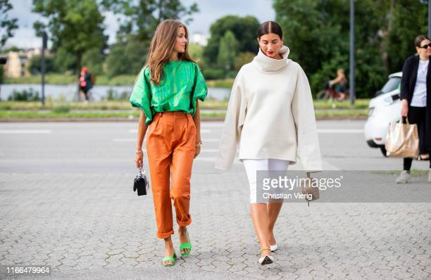 Nina Sandbech is seen wearing orange pants green top black white Boyy bag and Katarina Petrovic is seen wearing white turtleneck white pants outside...