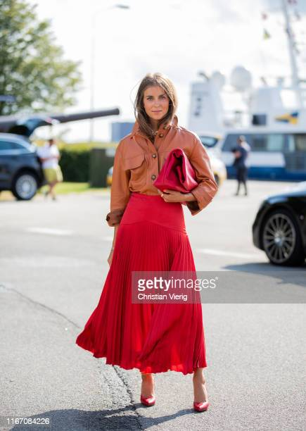Nina Sandbech is seen wearing red pleated skirt orange leather button shirt outside Stine Goya during Copenhagen Fashion Week Spring/Summer 2020 on...