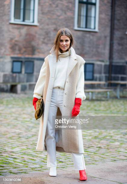 Nina Sandbech is seen wearing sleeveless coat, red gloves, brown clutch, turtleneck, white pants, two tone red white ankle boots outside Mfpen during...
