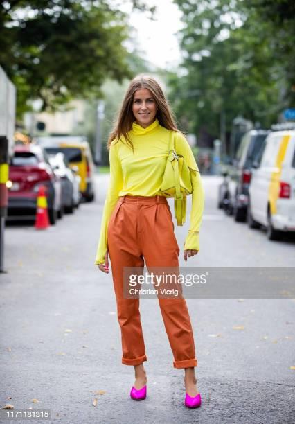 Nina Sandbech is seen wearing yellow Loewe bag yellow turtleneck rusty orange pants pink heels during Oslo Fashion on August 30 2019 in Oslo Norway