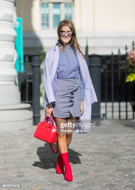 Nina Sandbech wearing checked blouse and skirt red Givenchy bag red sock boots outside Stylein on August 30 2017 in Stockholm Sweden