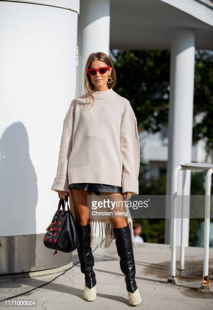 Nina Sandbech wearing oversized knit two tone boots leather shorts Loewe bag during Oslo Fushion on August 29 2019 in Oslo Norway