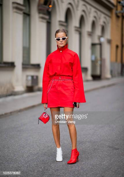 Nina Sandbech wearing red jacket and skirt blue white ankle boots during Stockholm Runway SS19 on August 30 2018 in Stockholm Sweden