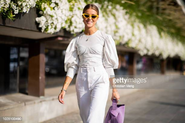 Nina Sandbech wearing white blouse, white cropped pants, ankle boots, purple bag is seen during Stockholm Runway SS19 on August 29, 2018 in...