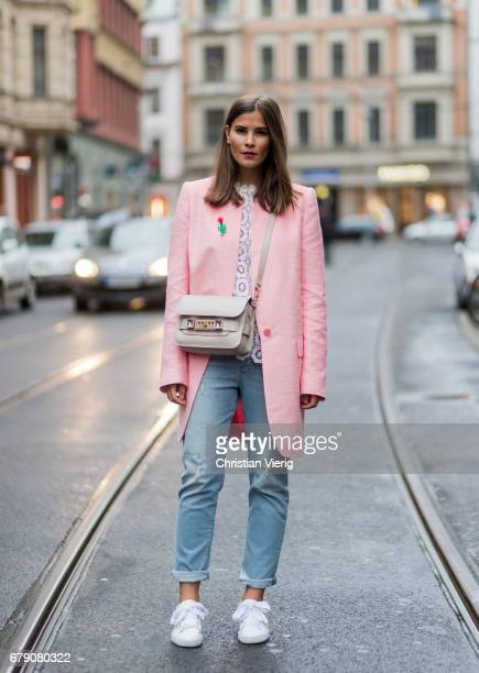 Nina Schwichtenberg wearing a pink coat Valentino bag a OhhCouture x Mavi denim jeans white sneakers on May 4 2017 in Berlin Germany