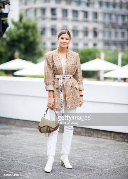 Nina Schwichtenberg wearing Dior bag belted plaid blazer white pants ankle boots is seen outside Der Berliner Salon during the Berlin Fashion Week...