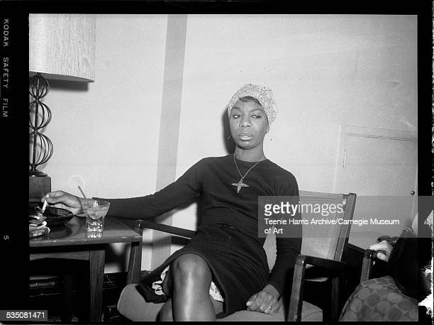 Nina Simone wearing paisley head scarf and cross pendant seated in chair tapping ashes from cigarette into ashtray Pittsburgh Pennsylvania 1962