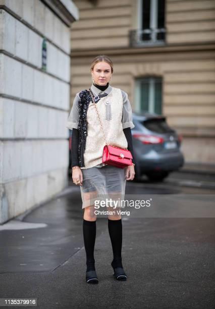 Nina Suess is seen weairng red bag sheer dress knee socks outside Miu Miu during Paris Fashion Week Womenswear Fall/Winter 2019/2020 on March 05 2019...