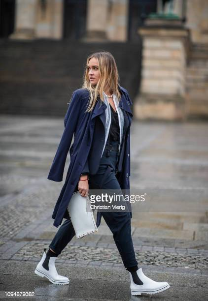 Nina Suess is seen wearing total look Marc Cain including white clutch navy trench coat navy blazer white zip jacket black top navy high waist pants...
