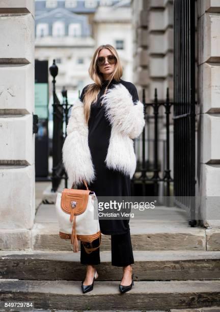 Nina Suess wearing a black Marc Cain dress Marc Cain backpack white Marc Cain jacket black pants and slingbacks Marc Cain during London Fashion Week...