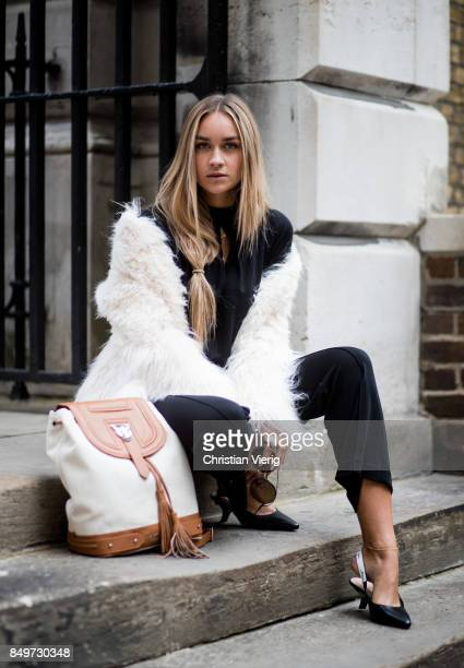 Nina Suess wearing a black Marc Cain dress Marc Cain backpack white Marc Cain jacket black pants and slingbacks Marc Cain during London Fashion Week...