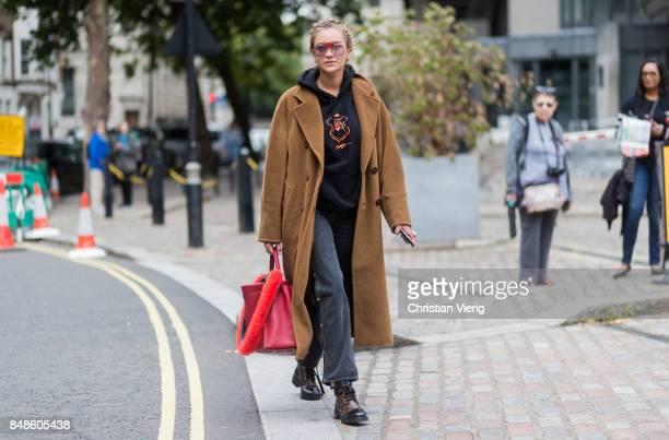 Nina Suess wearing brown wool coat hoody red Fendi bag outside Preen during London Fashion Week September 2017 on September 17 2017 in London England
