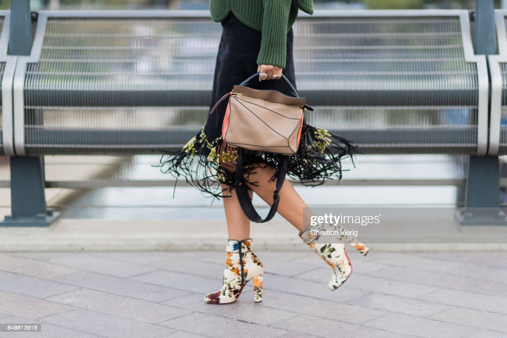 Nina Suess wearing Loewe bag, skirt with fringes, ankle boots, green knit outside Versus Versace during London Fashion Week September 2017 on September 17, 2017 in London, England.