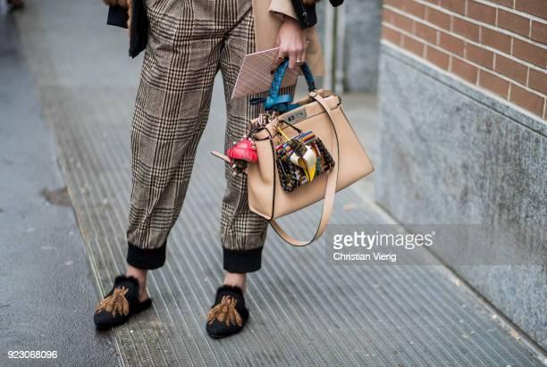 Nina Suess wearing plaid pants cropped top Fendi jacket and bag seen outside Fendi during Milan Fashion Week Fall/Winter 2018/19 on February 22 2018...