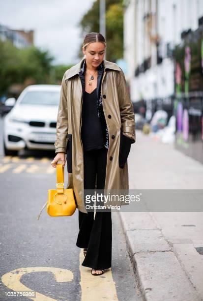 Nina Suess wearing yellow bag black flared pants trench coat is seen outside Natasha Zinko during London Fashion Week September 2018 on September 18...