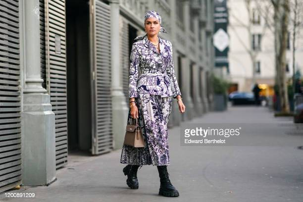 Nina Suess wears a wax headscarf, earrings, a pearl necklace, a bracelet, a Christian Dior black and white wax jacket and pleated skirt, a...
