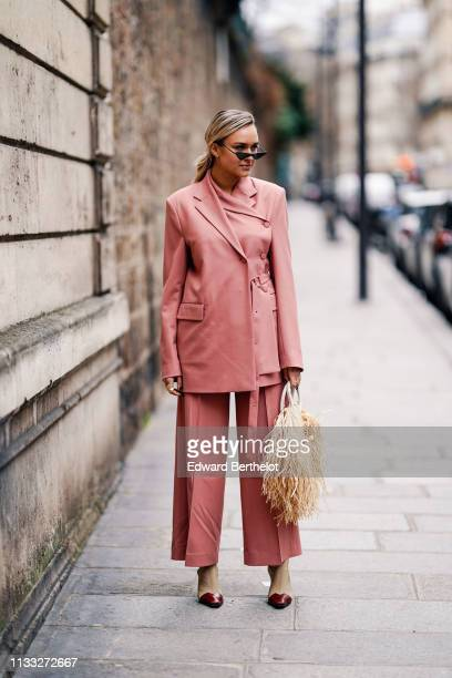 Nina Suess wears sunglasses a long pink blazer jacket a Jacquemus rattan fringed bag flared pants shoes with burgundy heels outside Elie Saab during...
