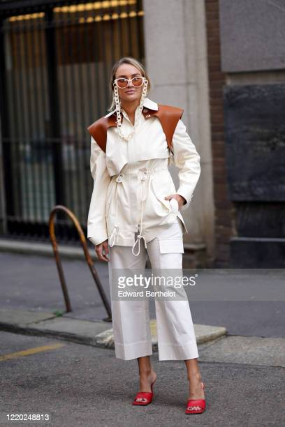 Nina Suess wears white sunglasses with a chain, a white jacket with brown leather shoulder pads, white cropped pants, red sandals, outside Sportmax,...