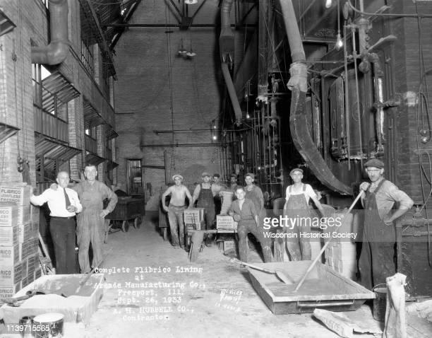 Nine brick layers with supervisor in engine room Freeport Illinois September 26 1933 Caption on print reads 'Complete Plibrico Jointless Firebrick...