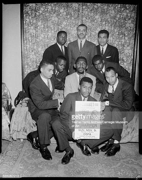 Nine men posing around broadside advertising show with Ahmad Jamal and Walt Harper in room with floral curtains and slipcovers Pittsburgh...