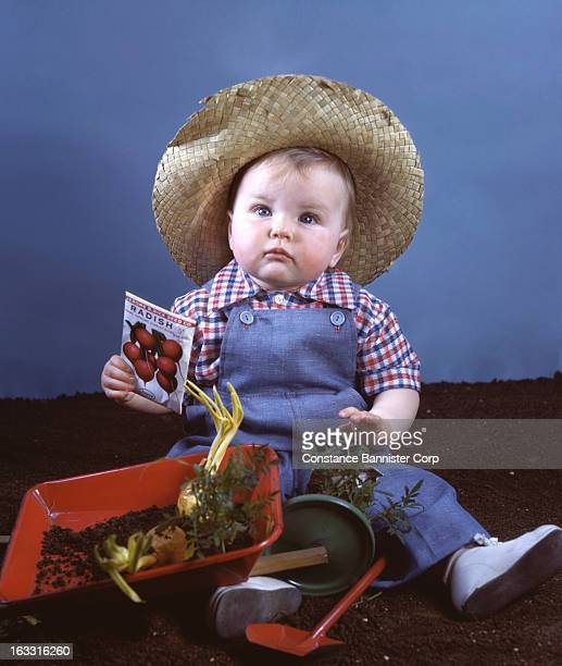 Nine month old baby boy wearing hat and overalls playing in the garden New York City