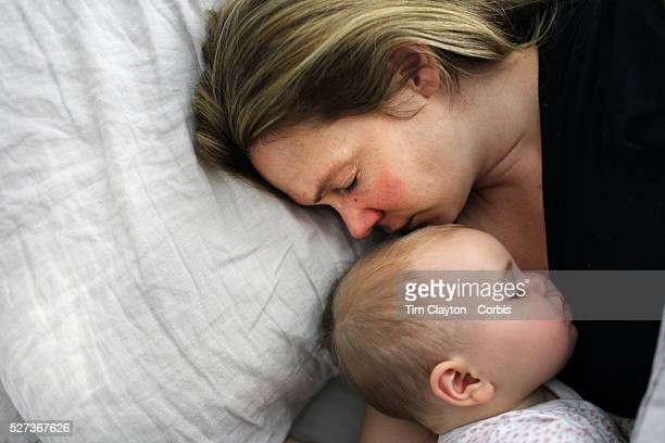A nine month old baby girl is cuddled by her mother while asleep in bed Photo Tim Clayton