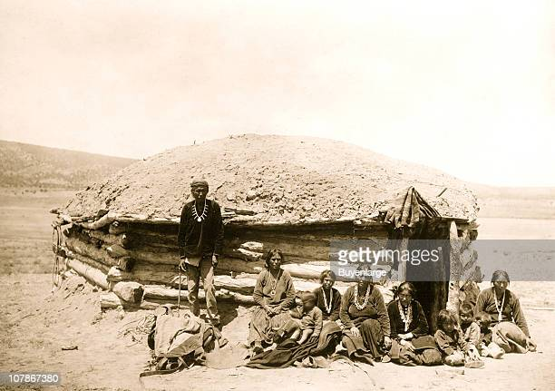 Nine Navajo Indians adults and children posed outside of hogan 1906