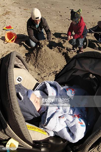 Nine weekold Oliver Vinson takes a nap in his stroller as cousin Ethan Moore and aunt Heather Moore visiting from Scotland make a sand castle at...