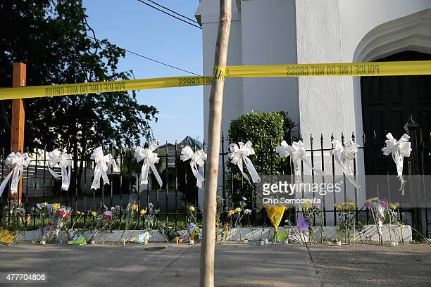 Nine white ribbons for the nine victims of the Emanuel African Methodist Episcopal Church shooting are tied to the fence outside the chruch June 19,...