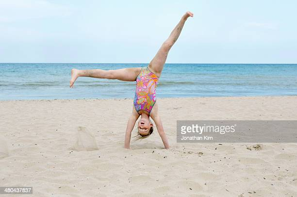 nine year old girl cartwheels on sandy beach - girl with legs spread stock photos and pictures