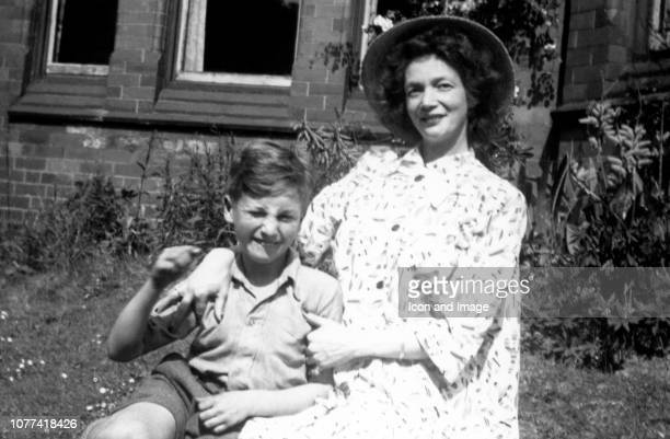 Nine year old John Lennon poses for a portrait with his mother Julia in the front garden of Ardmore which was the name of the home of John's cousin...