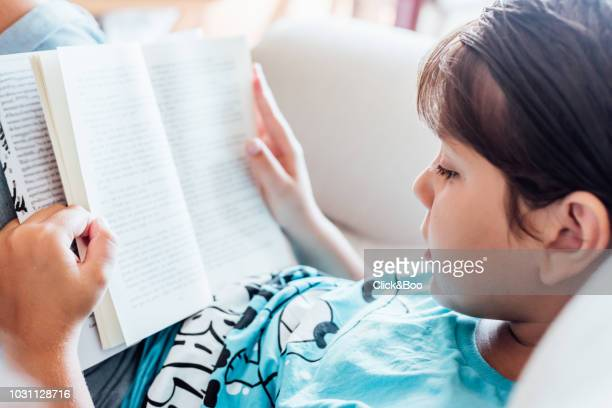 nine years old kid reading a book indoors (home interior) - 8 9 years stock pictures, royalty-free photos & images