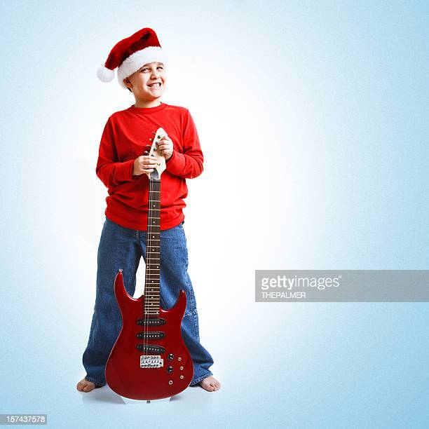 nine years old santa kid with red guitar