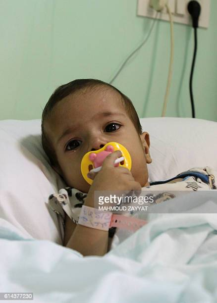 Ninemonthold Syrian refugee Amena alHelou is seen lying in a hospital bed prior to having an operation on her heart at the Hammoud Universal Hospital...