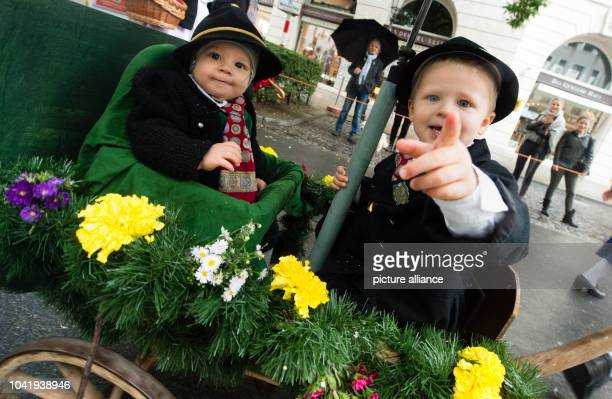 Ninemonthsold Alois and his threeyearold brother Jakob are carried in a cart at the traditional Trachten costume and marksmen parade on the...