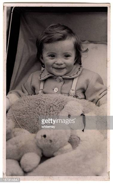 Nineteen forties baby in pram, with teddy bear