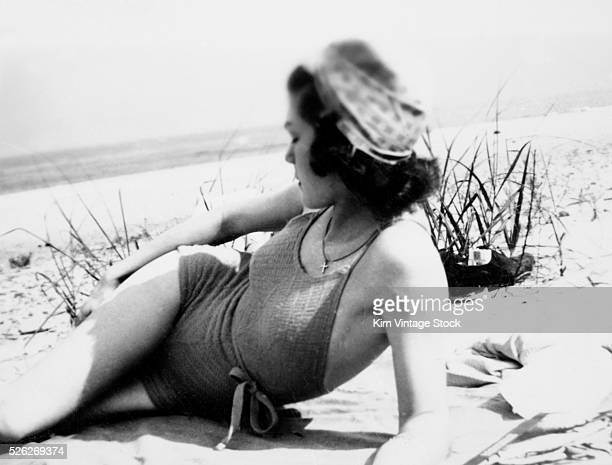 Nineteen year old girl lays at the beach in her swimming suit