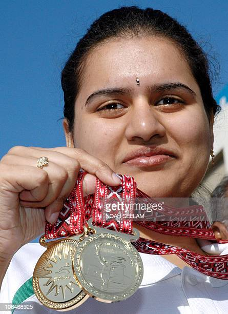 Nineteenyear old Indian woman Koneru Humpy of Vijayawada Andhra Pradesh shows off her gold medals upon her arrival at Hyderabad's airport from Doha...