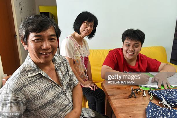Nineteenyearold Singaporean youth See Toh Sheng Jie poses with his parents Jason and Wendy at their home in Singapore on August 5 2016 The autistic...