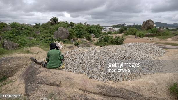 Ninety fouryearold grand mother Azumi Atang breaks stones to make a living in Jos Plateau State in central Nigeria on August 24 2019 Many her age lie...
