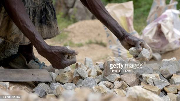 TOPSHOT Ninety fouryearold grand mother Azumi Atang picks up stones she has been breaking with a hammer to make a living in Jos Plateau State in...